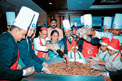 Mayor Pushpalatha Chikanna and Bishop of Mysore Thomas A Vazhapally stir ingredients for the preparation of Christmas cake at a cake mixing event held in Mysore recently. dh photo