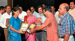 reward: Medical education and district-in-charge minister S A Ramdas presents mementos to teachers at a programme held in Mysore on Tuesday to honour schools that secured 100 per cent results in SSLC exams during the last academic year. Dh photo