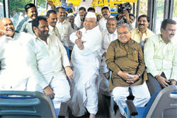 Show of strength: Minister Revu Naik Belamagi flexes his muscles as other BJP legislators watch him on their way to a  resort on the outskirts of the City, ahead of the bypoll to the Legislative Council on Wednesday. DH Photo