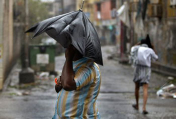 A man stands with an umbrella during heavy winds in Pondicherry, India, Friday, Dec. 30, 2011. India's weather office has warned residents along parts of the country's southeastern coast that Cyclone Thane is likely to cause heavy rains and gale-force winds. AP