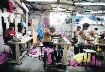 Abysmal conditions: Workers sew clothes in a garment factory owned by Mohammad Mustaqueem, in Dharavi slum, Mumbai. More than a warehouse for the poor,  Dharavi contains a hive of workshops with an annual economic output of more than Rs 3000 crore. NYT