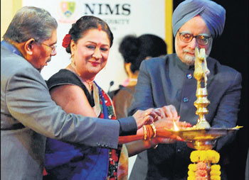 Prime Minister Manmohan Singh and Minister for Overseas Indian Affairs Vayalar Ravi (L) help Trinidad and Tobago Prime Minister Kamala Persad Bissessar to light a lamp during the opening ceremony of the 10th Pravasi Bharatiya Divas 2012 in Jaipur on Sunday. AFP