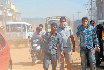 The dust rising from the road is literally suffocating the commuters and pedestrians in Chikmagalur. DH PHOTO