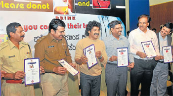 DCPs P Rajendra Prasad and Basavaraj Malagathi, actor Upendra, police commissioner Sunil Agarwal, MCC commissioner K S Raykar and Airtel CEO Rohit Malhotra release the stickers of 'Namma Shaale Police' in Mysore on Friday. DH Photo