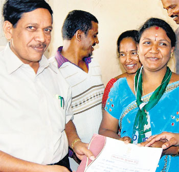 Assistant Commissioner R S Peddappaiah hands the election certificate to JD(S) candidate L Asha, who won the ZP bypoll from Vemagal in Kolar on Friday. dh photo
