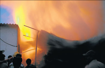 Fire fighters extinguish fire at a plywood godown at Bannimantap industrial area in Mysore on Sunday. DH photo