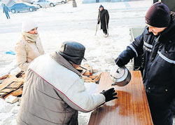 A social employee gives out a hot meal and hot tea to an elderly man at one of the newly opened shelters in the western Ukrainian city of Lviv on Monday. AFP