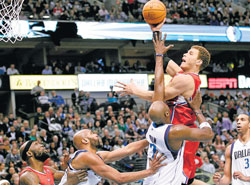 sharp Los Angeles Clippers' Blake Griffin (second from right) shoots past Dallas Mavericks' Lamar Odom during their NBA game in Dallas on Monday. AP