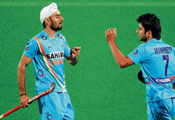 Hat-trick man: India's Gurvinder Singh Chandi (left) celebrates with team-mate Manpreet Singh after scoring against Singapore in New Delhi on Saturday. AFP