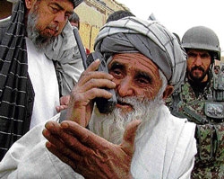 IRREVERSIBLEDAMAGE: Abdul Samad,whohad 11 relatives killed by an American soldier, uses a phone to speak with Afghan President Hamid Karzai outside hishomein Panjwai, Afghanistan on Sunday. NYT