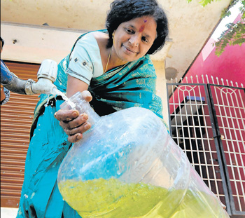 Not potable: A resident of Rajagopalnagar shows water drawn from a public tap in the area that is green in colour, due to chromium contamination. DH Photo