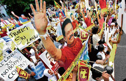 Supporters of the Sri Lankan government display pictures of President Mahinda Rajapaksa while protesting outside British embassy to denounce a resolution proposed by UN Human Rights Council on human rights abuses by the Sri Lankan government during the country's civil war, in Colombo, Sri Lanka, on Tuesday. AP