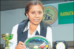 Umadevi poses with her World billiards and   senior snooker titles in Bangalore on Friday. DH PHOTO