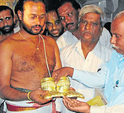 Tahsildar Shivanagaiah hands over the golden padukas to the temple priest Ravikumar Supardi at B R Hills in Yalandur on Tuesday.