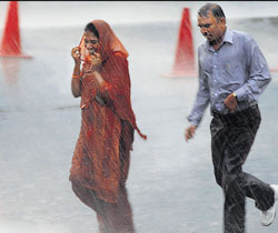 Pedestrians run for cover from rain which lashed the city on Friday. DH Photo