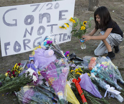 A girl leaves flowers at a memorial near theater where 12 people were killed July 20, 2012 in Aurora, Colorado. A graduate student who told police he was the Joker opened fire in a theater showing the premiere of the latest Batman movie near Denver. AFP