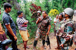 KEEPING POSTED: Alok Kumar, IGP of the Anti-naxal Force, interacts with a resident of Subramanya. DH Photos