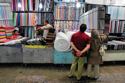 shattered dreams: A fabric merchant at Tehran's main bazaar in July. Some of the merchants there have closed shop to protest a crackdown on sidewalk money changers this week. AP