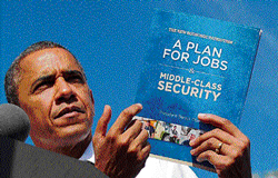 US President Barack Obama shows a copy of his jobs plan as he speaks during a campaign rally in Florida. AFP