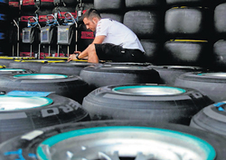 A technician prepares tyres outside the garage of a team at the BIC on Thursday. Reuters