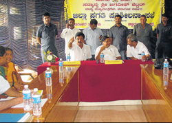 Chief Minister Jagadish Shettar chairing a review meeting, at SJM College in Tarikere                           on Saturday. District-in-Charge Minister Jeevraj, MLA D S Suresh, DC Anjankumar and others look on.