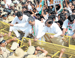 in defiance: State Youth Congress president Rizwan Arshad, CLP leader Siddaramaiah and KPCC president G Parameshwara try to jump over the barricade put up by the police during a protest against the State government in Bangalore on Saturday. DH Photo