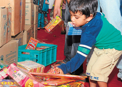 It's my share: A kid toys with crackers at a stall set up at Attibele bordering Tamil Nadu  on Sunday. DH Photo