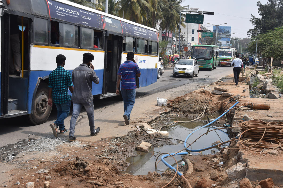 People struggle to walk due to no footpath and sewage water flow on road at Hulimavu gate, Bannerghatta Main Road in Bengaluru on Sunday. Photo by S K Dinesh