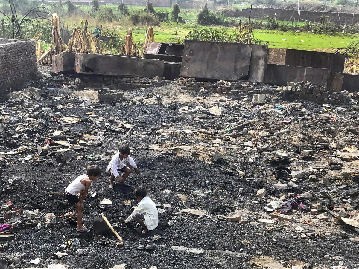 Children searching for their belongings in the charred debris of their homes, a week after a Rohingya camp caught fire in Sarita Vihar in New Delhi. PTI Photo