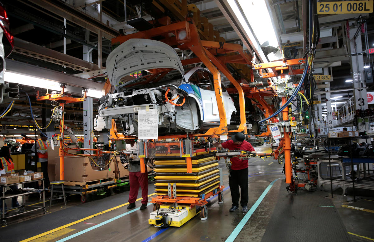 General Motors assembly workers connect a battery pack underneath a partially assembled 2018 Chevrolet Bolt EV vehicle on the assembly line at Orion Assembly in Lake Orion, Michigan, U.S., March 19, 2018. Photo taken March 19, 2018. REUTERS/Rebecca Cook