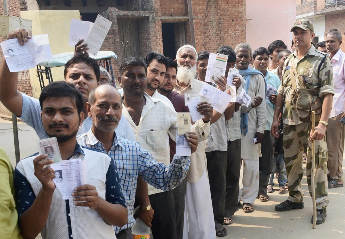 Voters show their voter identity cards as they wait in a queue to cast their votes for Noorpur Assembly bypolls, in Bijnor. PTI