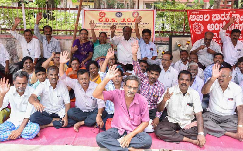 7th Day : Akila bharath Grameena Post Employees Sangha (AIGDUS) members staged dharna in front of PostOffice (Near Clock Tower) in Davangere on Monday. Demanding to settle the 7th Wage revision and so on demands. Manjunath led the dharna (28-05-18), Photo By : Anup R. Thippeswamy.