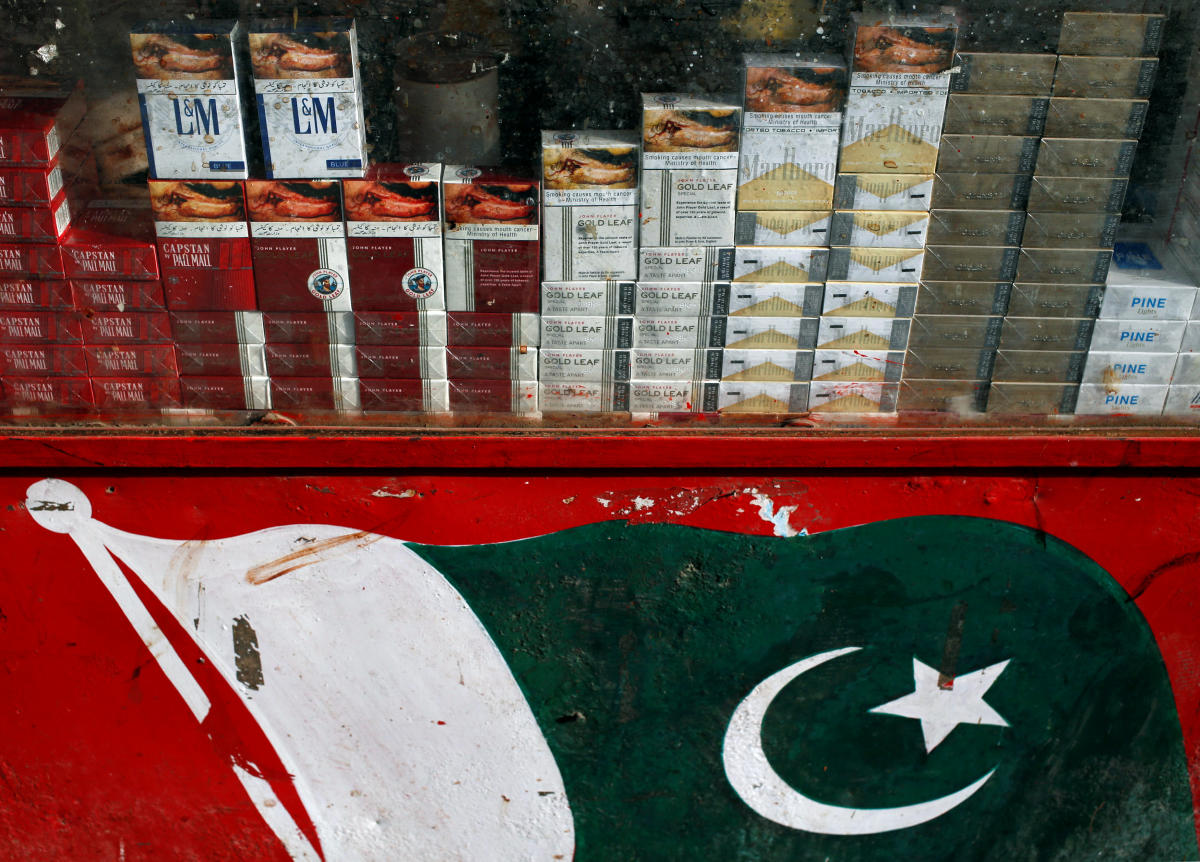 Brands of cigarette packs with health warning are displayed in the showcase of a kiosk painted with Pakistan's national flag, along a road in Karachi, Pakistan May 5, 2018. Picture taken May 5, 2018. REUTERS/Akhtar Soomro