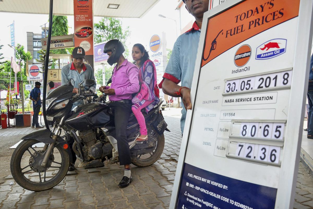 An employee attends to a customer at a petrol pump, as the prices of petrol and diesel keep showing volatility, in Guwahati on Wednesday. PTI