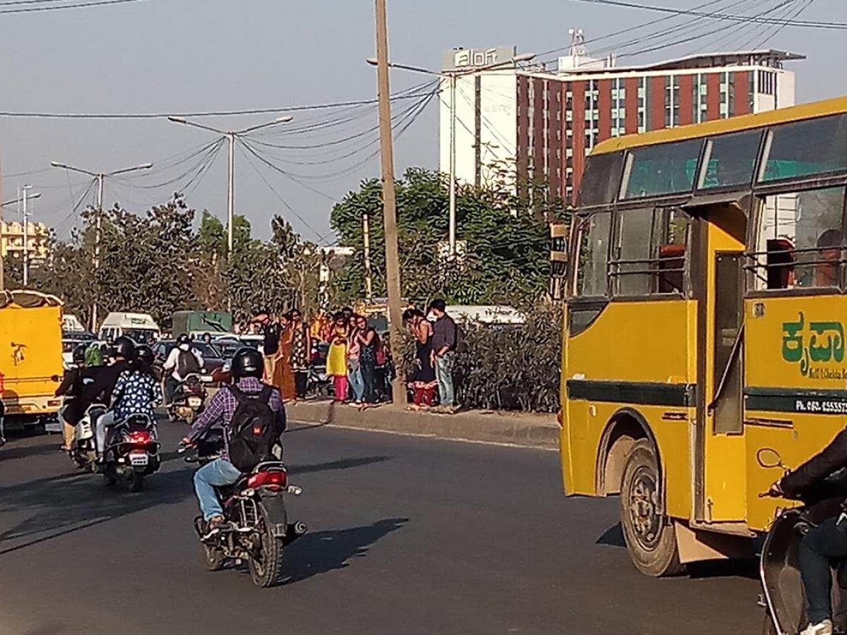 College students struggling to cross the busy ORR near Kadabeesanhalli, opposite New Horizon Engineering College.