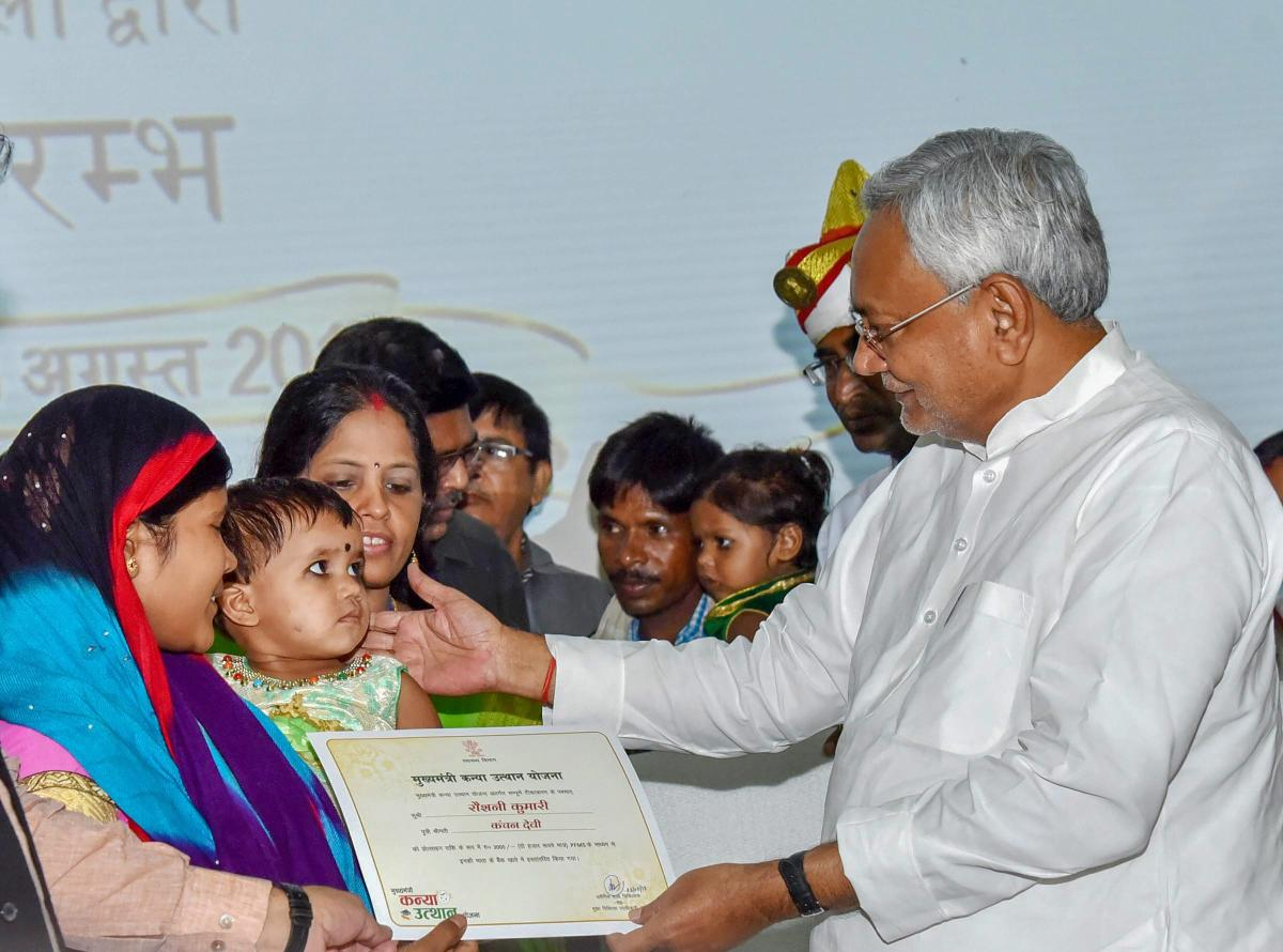 """Bihar Chief Minister Nitish Kumar gives away a cheque and a certificate to a beneficiary during """"Mukhyamantri Kanya Utthan Yojana"""" (Girls Empowerment Scheme), at Adhiveshan Bhawan in Patna on Friday. (PTI Photo)"""