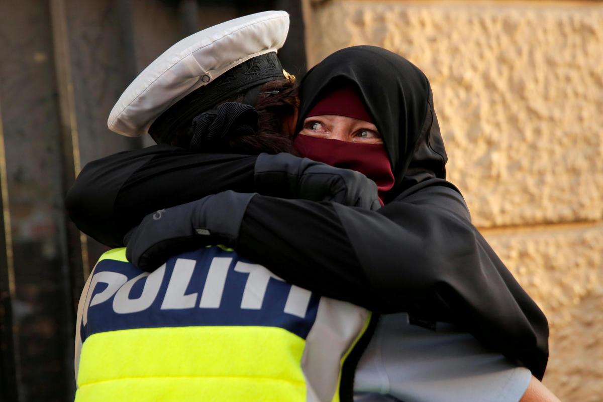 Ayah, 37, a wearer of the niqab weeps as she is embraced by a police officer during a demonstration against the Danish face veil ban in Copenhagen, Denmark, August 1, 2018. (REUTERS/Andrew Kelly)