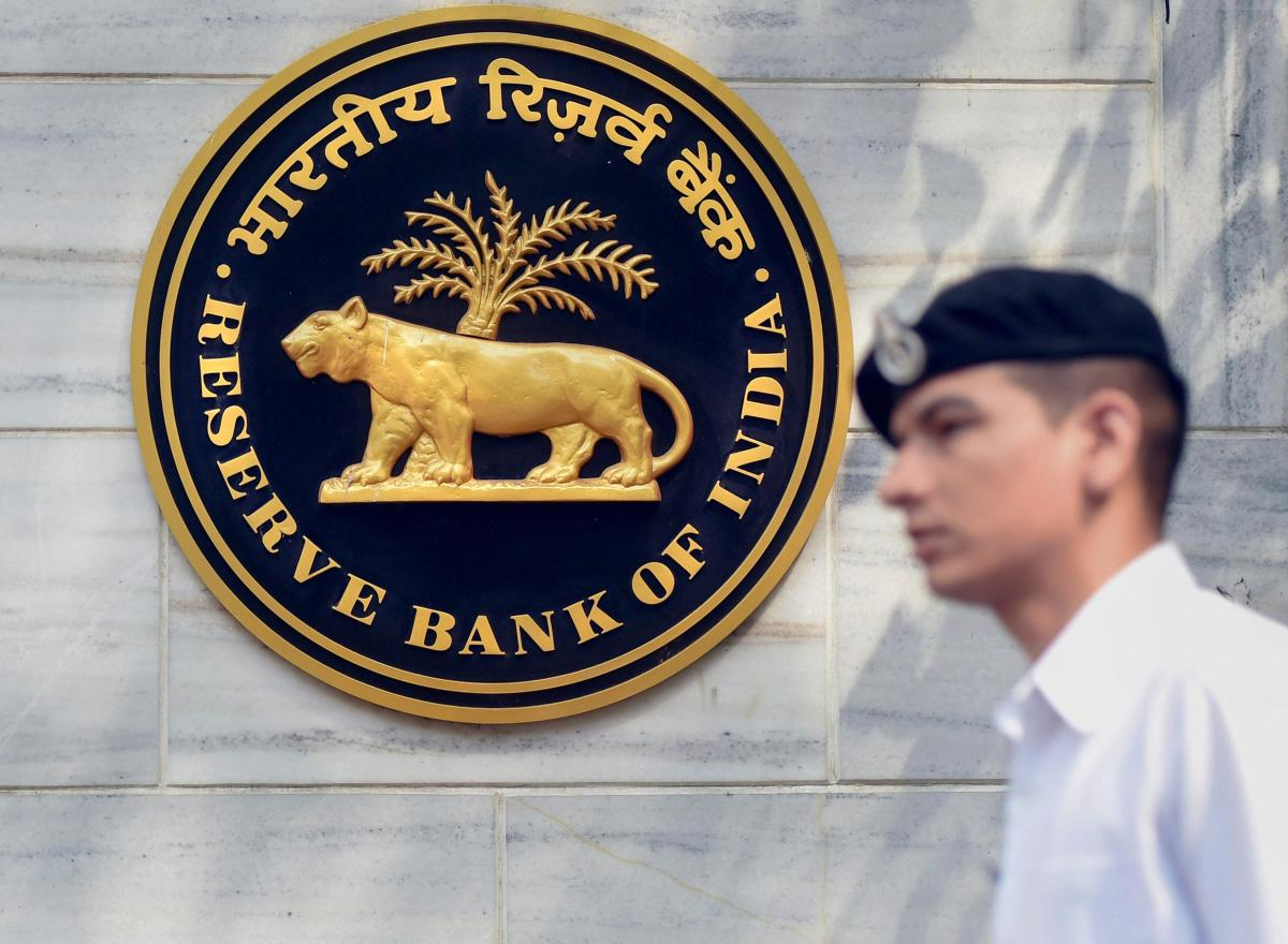 Mumbai: An Indian Navy officer walks past the emblem of Reserve Bank of India (RBI) at RBI head office in Mumbai on Thursday. PTI Photo by Shashank Parade(PTI4_5_2018_000197A)
