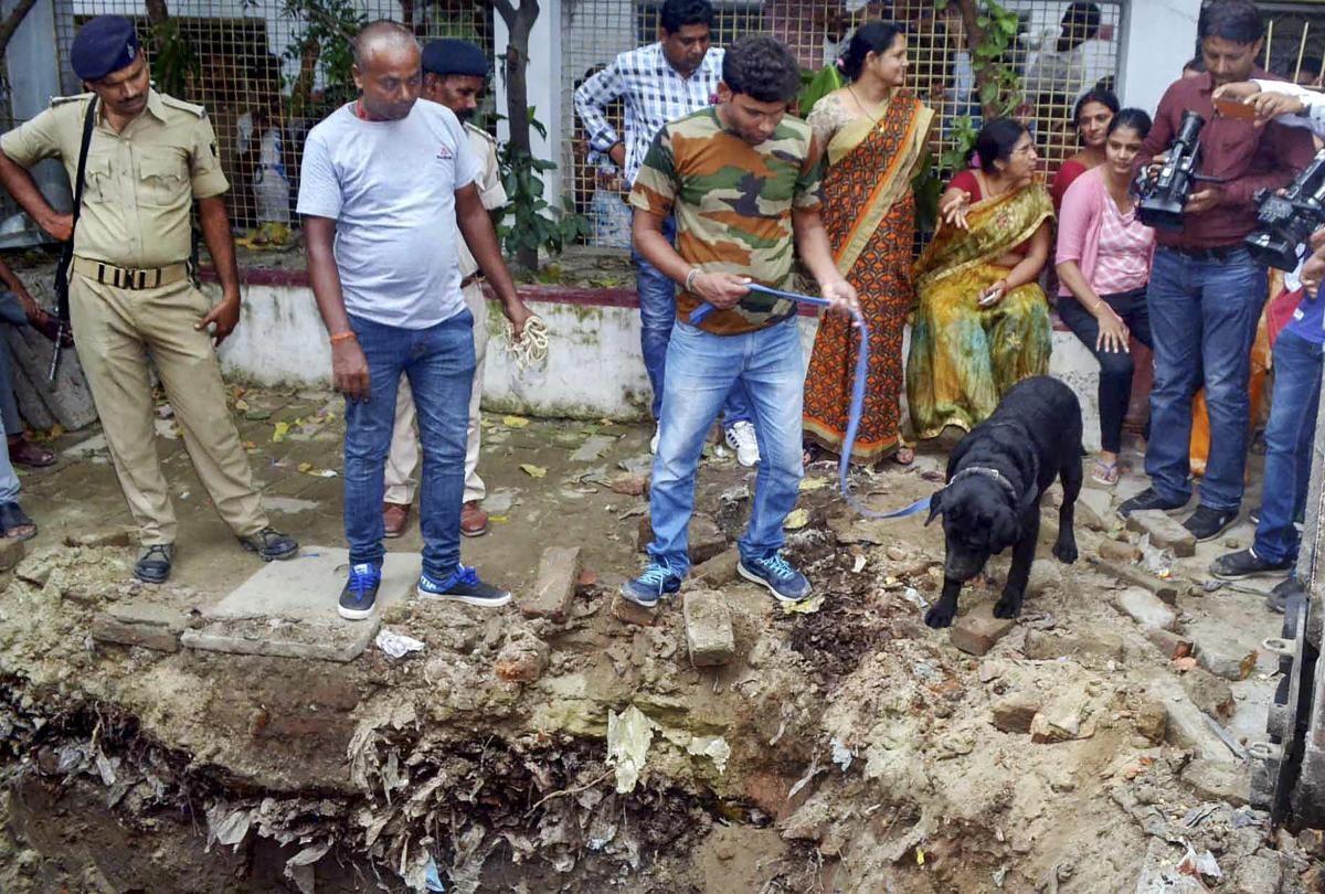 Muzaffarpur: Police with their sniffer dogs investigate the site where a rape victim was allegedly buried, at a government shelter home in Muzaffarpur, on Monday, July 23, 2018. A girl of the home has alleged that one of her fellow inmates was beaten to d