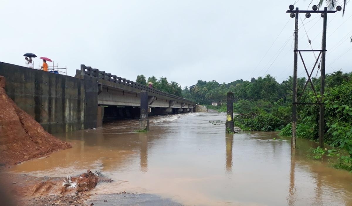 The inundated Hosamata bridge near Kadaba. As work on the new bridge is incomplete, vehicles use the old bridge.