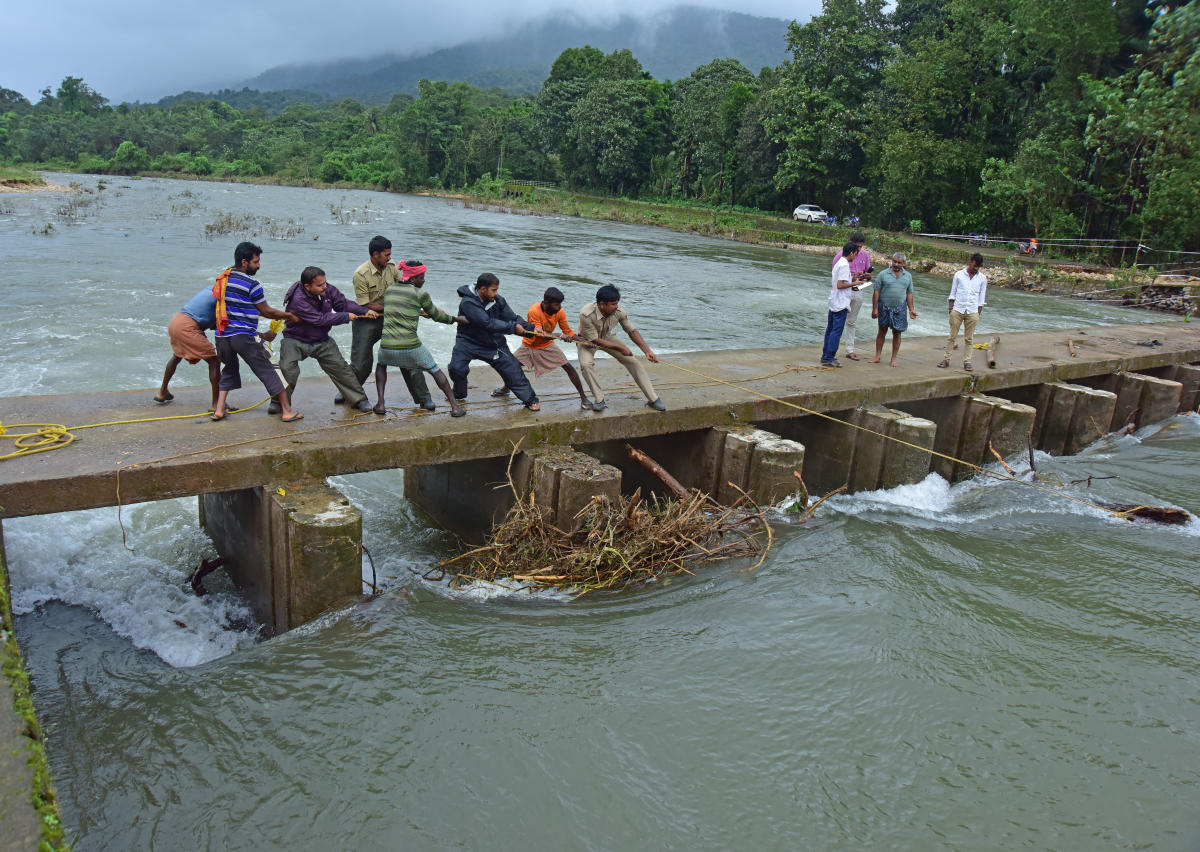 Locals join the police and Fire department personnel in clearing logs stuck at Kindi check dam built across Kapila river near Shishila in Belthangdy taluk. DH PHOTO/GOVINDRAJ JAVALI