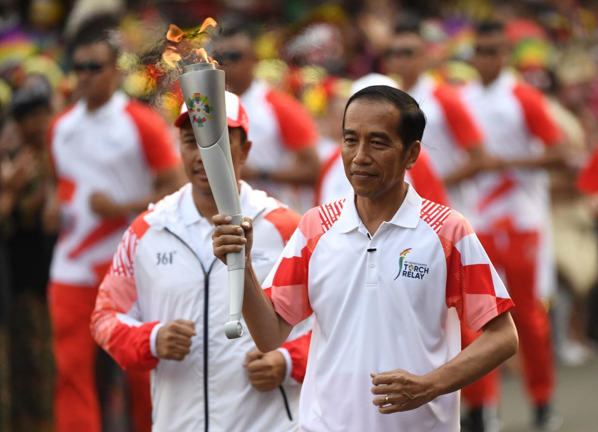 Indonesian President Joko Widodo carries the torch for the 2018 Asian Games in Jakarta on Friday. AFP