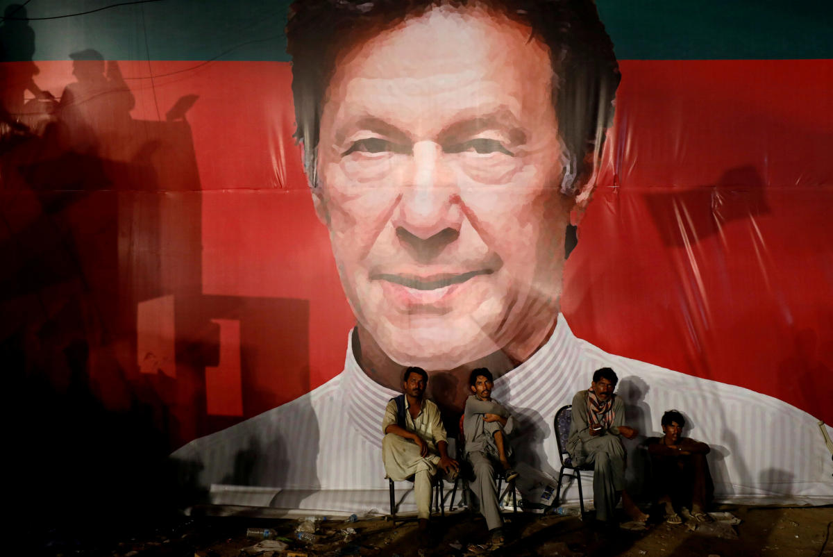 Labourers, sit under a wall with a billboard displaying a photo of Imran Khan, chairman of the Pakistan Tehreek-e-Insaf (PTI), political party, as they listen to him during a campaign rally ahead of general elections in Karachi, Pakistan. (Reuters File Photo)