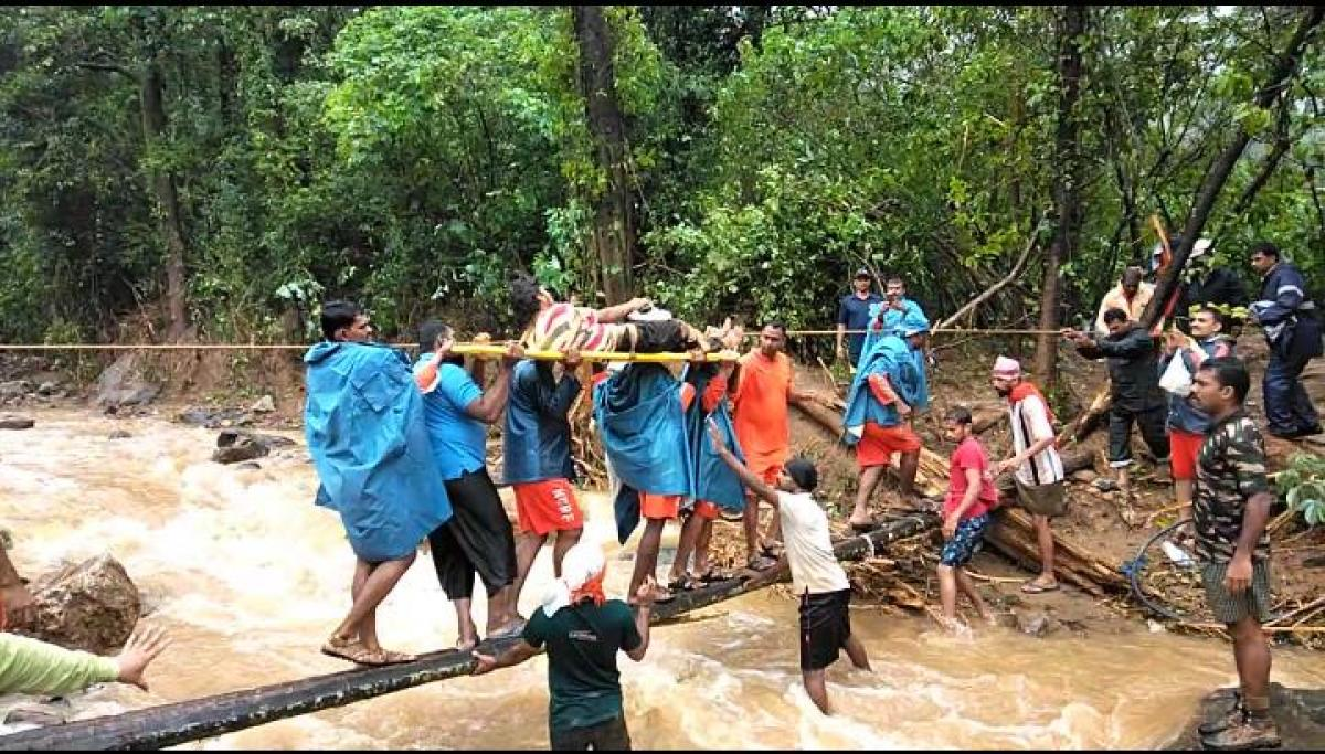 A stranded rubber plantation labourer is rescued by NDRF personnel. DH photo.
