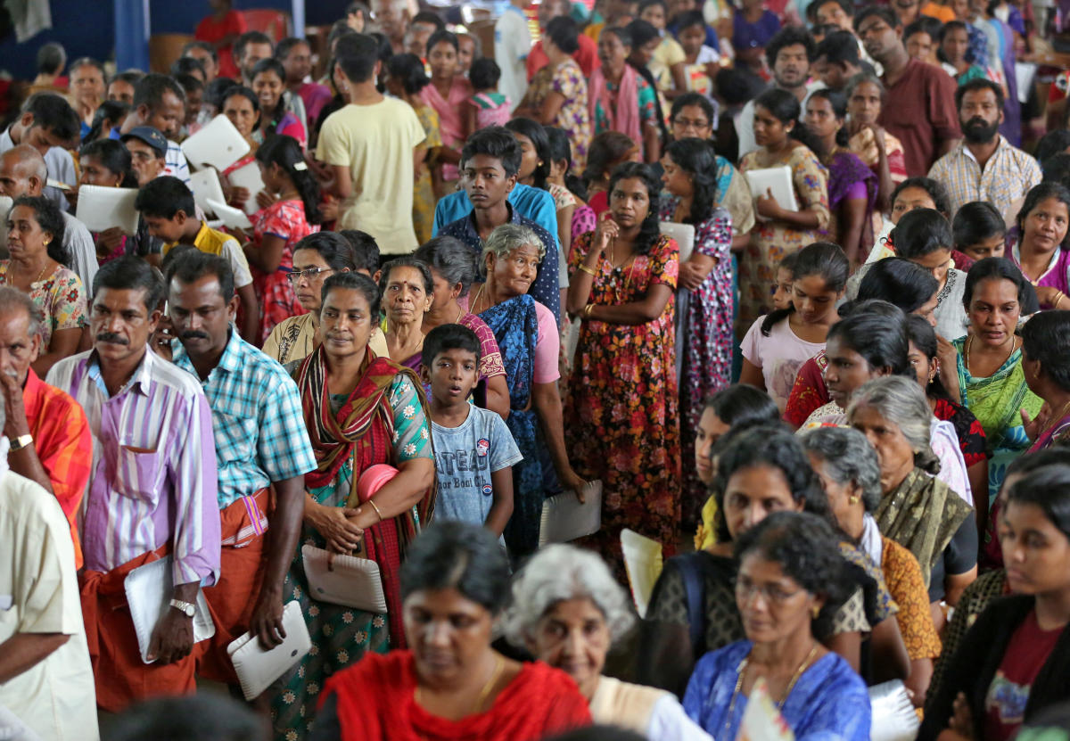 Flood-affected people wait to receive food inside a college auditorium, which has been converted into a temporary relief camp, in Kochi. Reuters photo