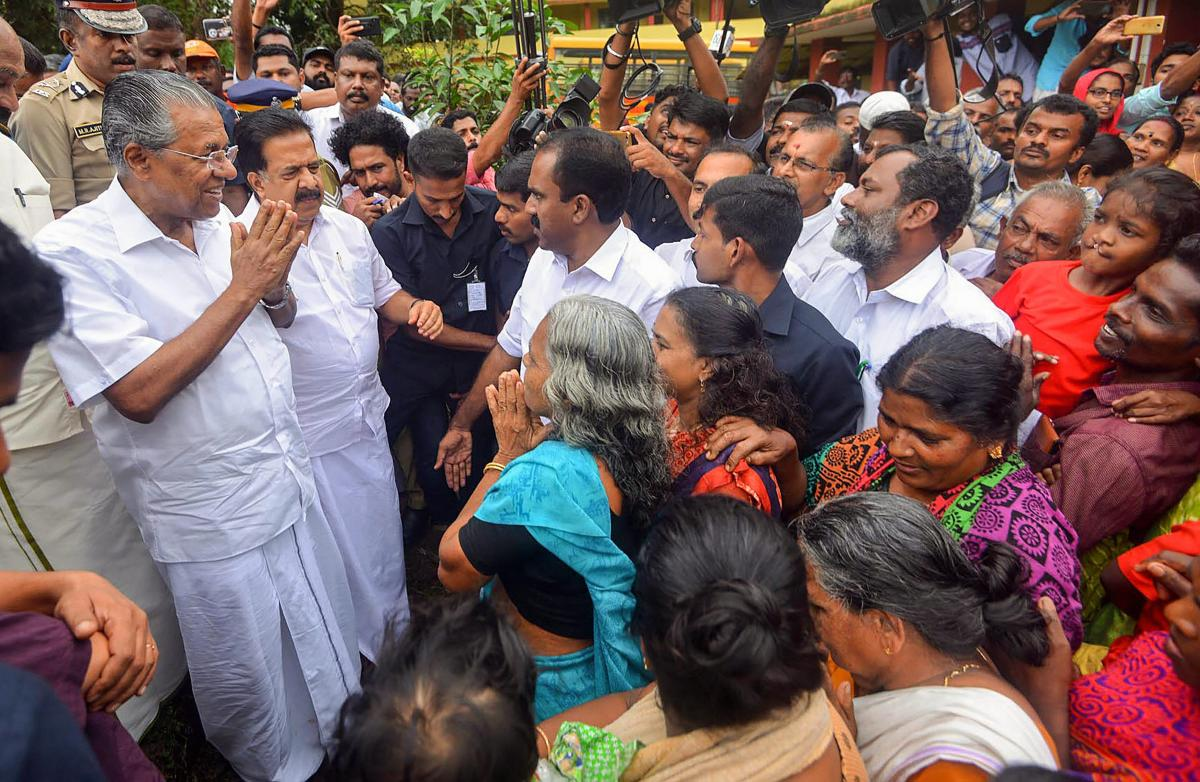 Kerala Chief Minister Pinarayi Vijayan interacts with the flood-affected people at a relief camp in Ernakulam on Saturday. PTI