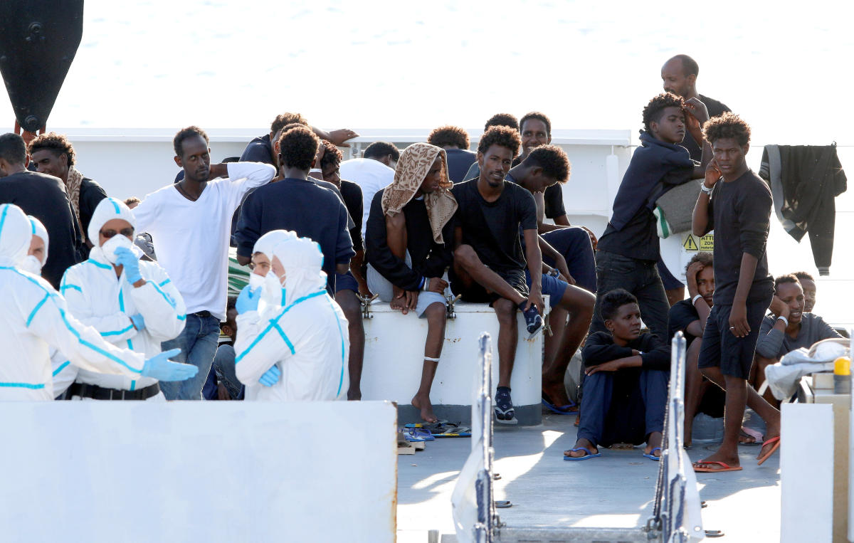 """Migrants wait to disembark from the Italian coast guard vessel """"Diciotti"""" at the port of Catania, Italy, August 22, 2018. Reuters"""