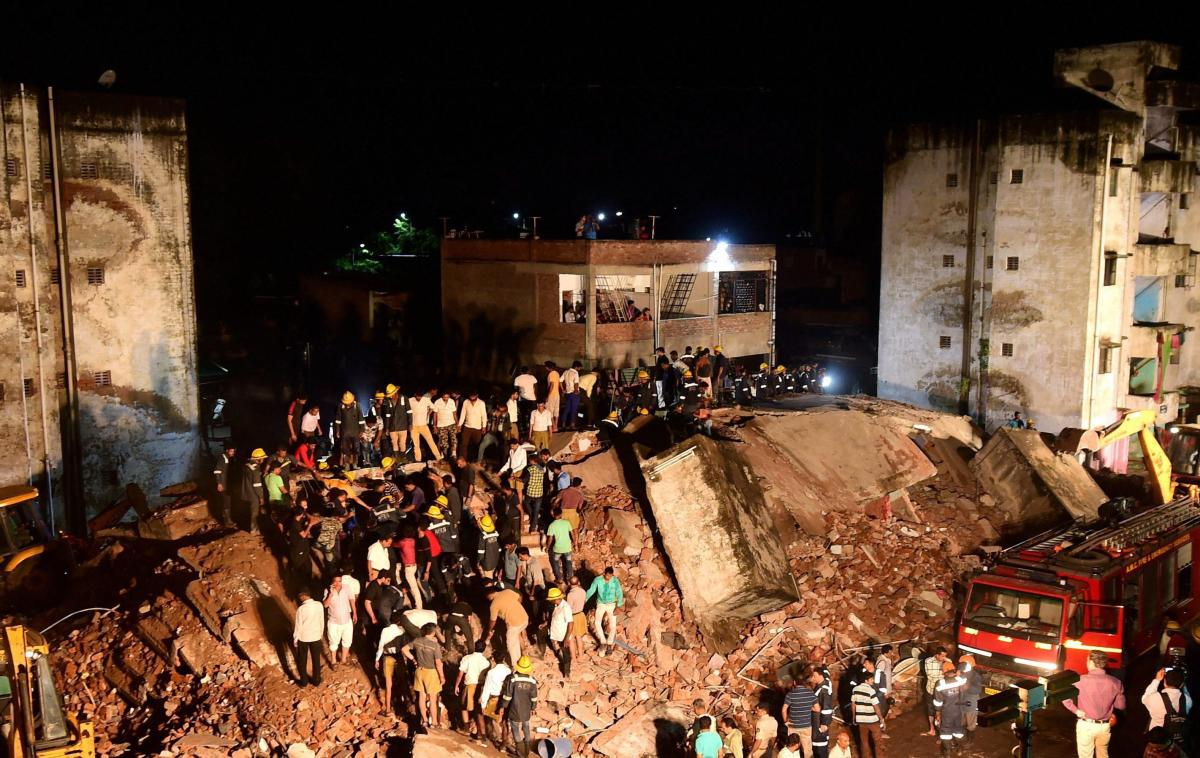 Firefighters and people try to clear the debris of the 4-floor government building which collapsed in Ahmedabad on Sunday. PTI