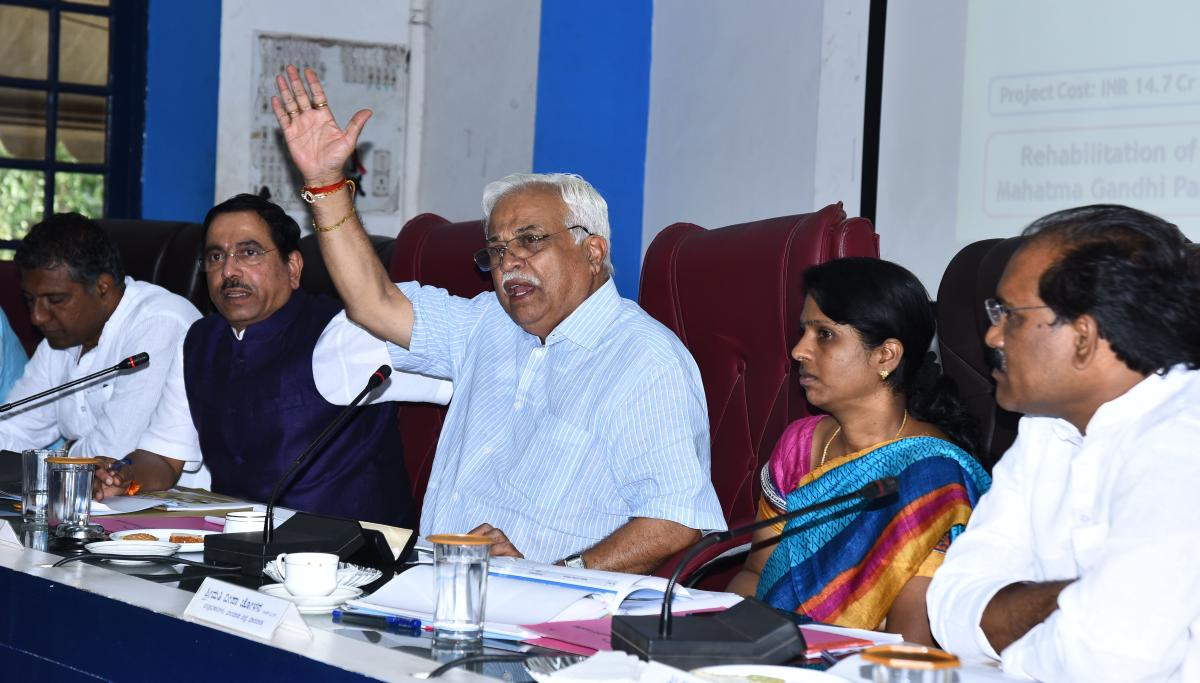 District In-charge Minister R V Deshpande speaks at 'Smart City' project progress review meeting held in Hubballi on Monday. MP Pralhad Joshi, DC Deepa Cholan, and others are present.