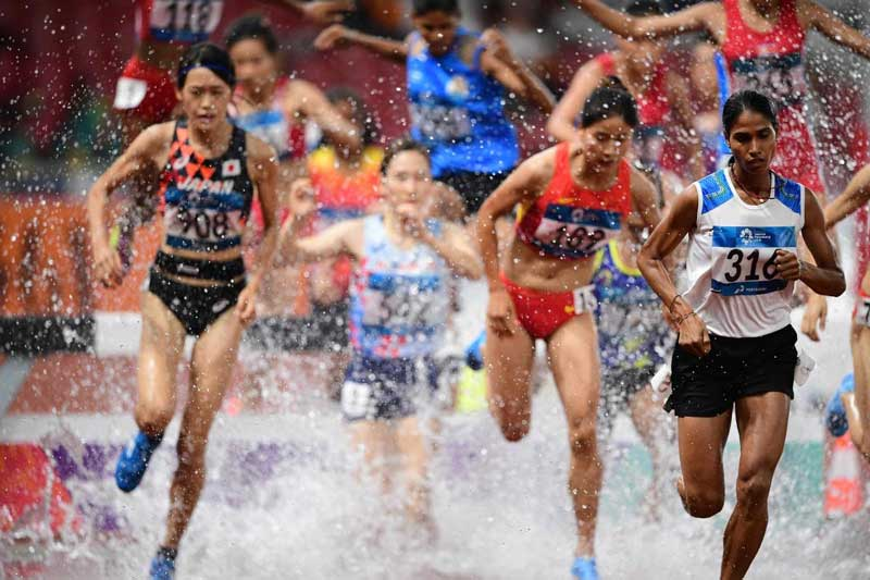 Sudha Singh (R) leads in the final of the women's 3000m steeplechase athletics event during the 2018 Asian Games in Jakarta. (AFP Photo)